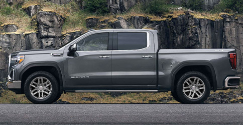 Side profile of a 2021 GMC Sierra 1500 parked in front of a mountain