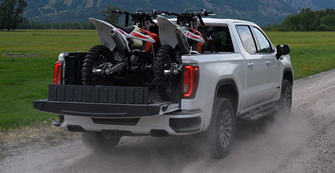 2021 GMC Sierra 1500 driving down a dirt road with dirt bikes in the trailer