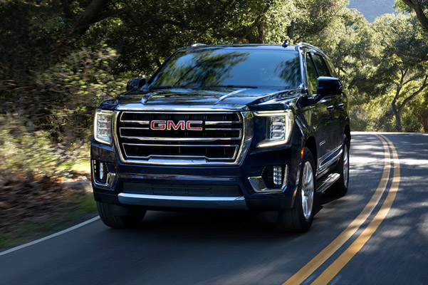 2021 GMC Yukon driving down wooded road