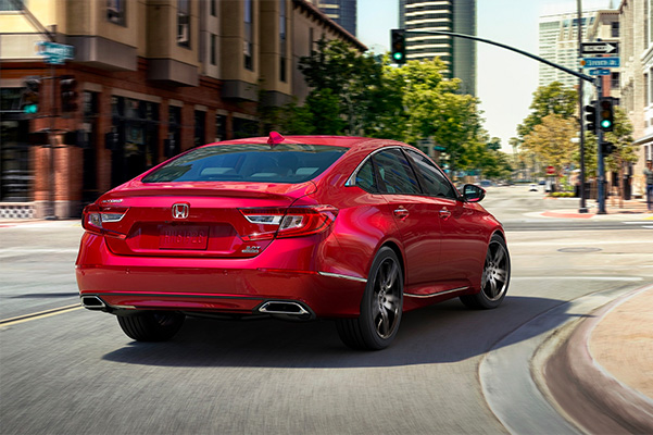 red 2021 honda accord showcasing adaptive damper system while taking a turn on a street curve