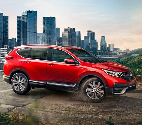 Passenger-side view of the 2021 CR-V Hybrid Touring in Radiant Red Metallic, driving from a city into a forest.