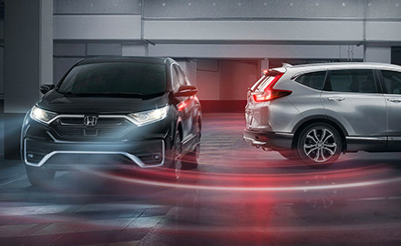 Front view of the 2021 Honda CR-V EX in Crystal Black Pearl driving in a parking structure as a CR-V Touring with available AWD in Lunar Silver Metallic attempts to back up, with illustrated lines demonstrating cross traffic monitor.