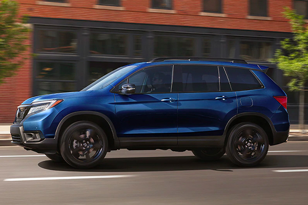 Driver-side profile view of the 2021 Honda Passport Elite in Obsidian Blue Pearl, driving by an urban brick building.