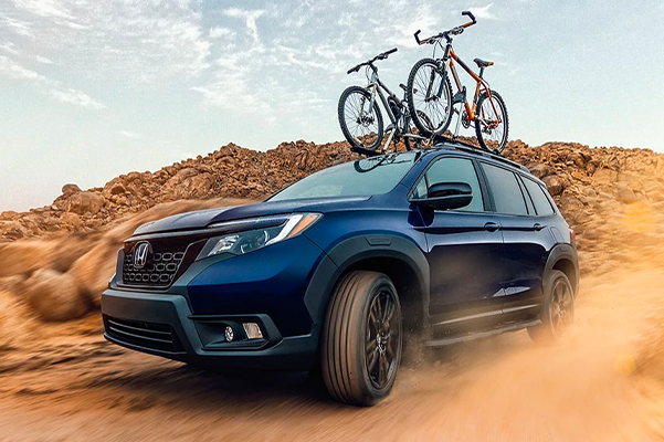 Front driver-side view of the 2021 Honda Passport AWD Sport, in Obsidian Blue Pearl with Honda Genuine Accessories, driving on dirt road, with two bikes stored on accessory frame mount bike attachment.
