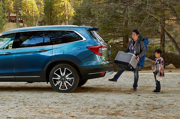 Side view of a 2021 Honda Pilot shown in Steel Saphire Metallic with a father and son packing it for a camping trip