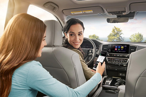 2021 Honda Pilot interior shown in gray leather with daughter showing mother how to connect her smart phone to the car