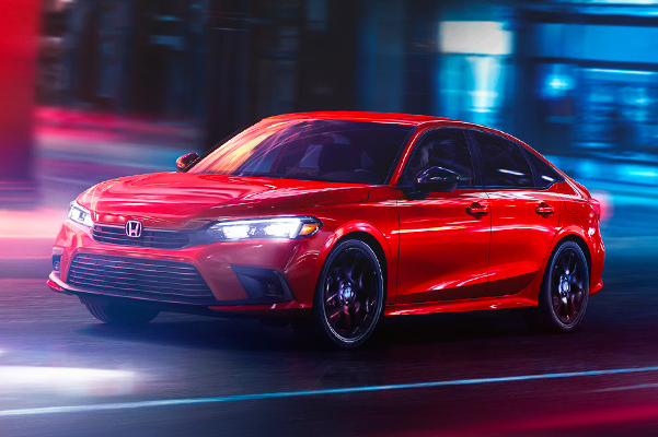 Front driver-side view of the 2022 Honda Civic Sport Sedan in Rallye Red, rounding a corner on a city street at night.