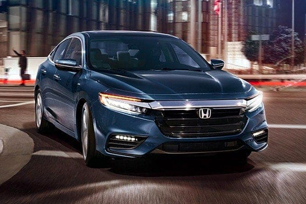 Front passenger-side view of 2022 Honda Insight Touring, in Cosmic Blue Metallic, driving on city road at night.