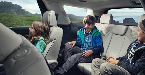 three kids smiling on the back seat of hyundai palisade suv