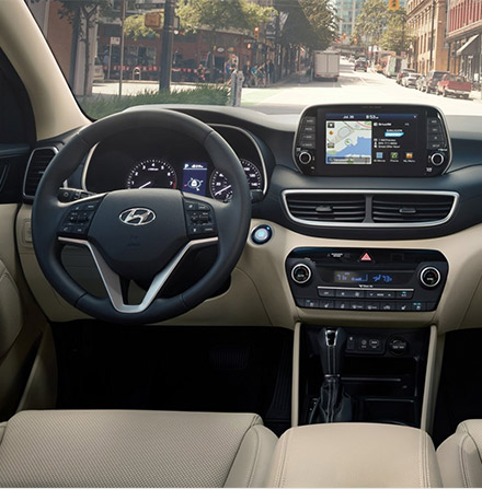interior view of Hyundai Tucson suv featuring dashboard, lether seats and digital navigation