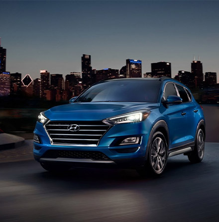 blue 2021 Tucson with LED Headlights on at night time on a city scene