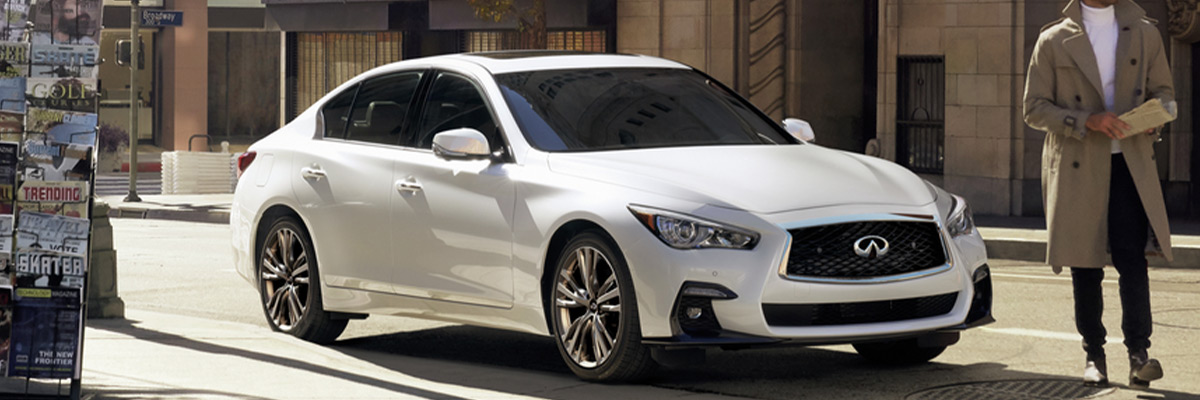 Man opening the door of a luxurious grand blue 2021 INFINITI Q50, showcasing its side profile.