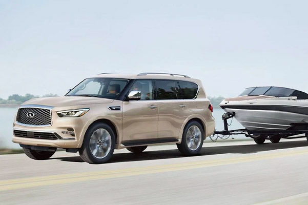 Exterior Driver Side View of 2021 INFINITI QX80 SUV Pulling Boat | Highlighting Engine Performance and Towing Capacity