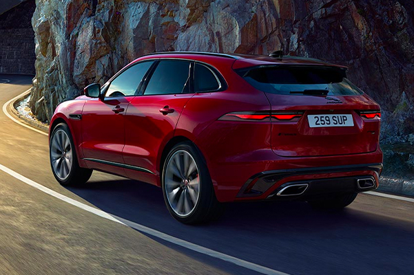 Red Jaguar F-PACE Driving on Winding Mountain Road.