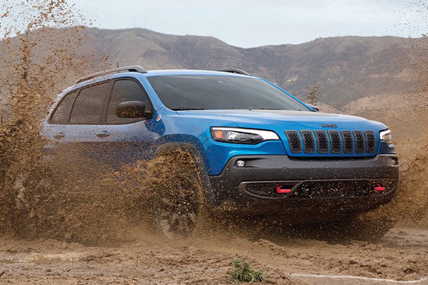 A 2021 Jeep Cherokee churns up mud from its wheels as it's driven off-road.