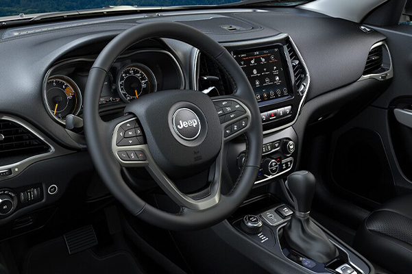 A close-up of the steering wheel and dashboard in the 2021 Jeep Cherokee.