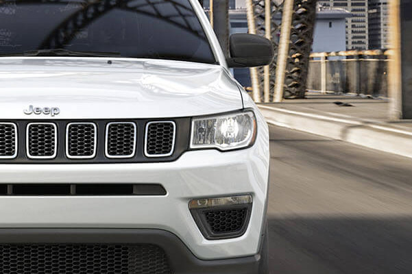 A head-on view of the 2021 Jeep Compass being driven over a bridge.