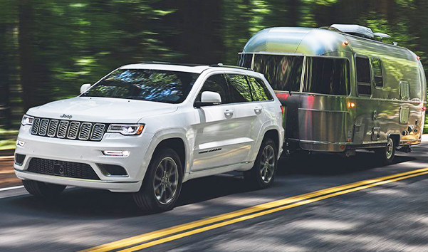The 2021 Jeep Grand Cherokee towing a travel trailer.