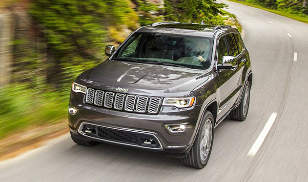 The 2021 Jeep Grand Cherokee Limited being driven around a bend in the road.
