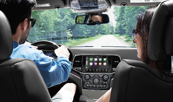 couple driving in 2021 Jeep Grand Cherokee with view of interior dashboard.