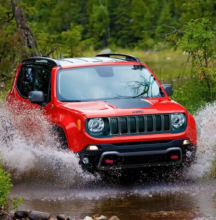 A red 2021 Jeep Renegade making a splash as it fords a stream.