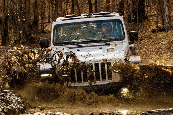 The 2021 Jeep Wrangler Rubicon being driven through a muddy stream.