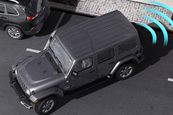Illustration of sensors monitoring the area behind the 2021 Jeep Wrangler Sahara as it parallel parks at a curb.