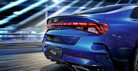 rear tail light view of the 2021 blue kia k5 zooming down the road