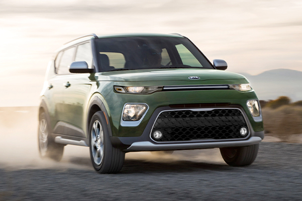 Green Kia Soul driving on a dirt road