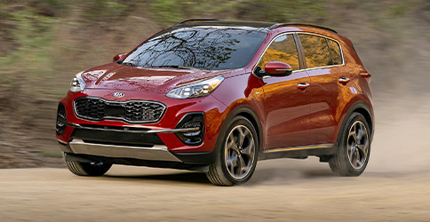 red 2021 kia sportage driving on the dirt
