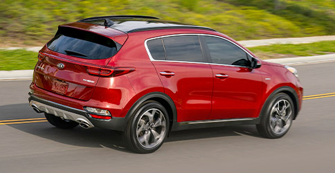red 2021 kia sportage driving down the road