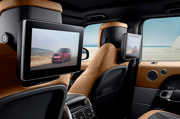 Interior shot of the back seat in a 2021 Range Rover Sport with flatscreens mounted on the back of the font seats