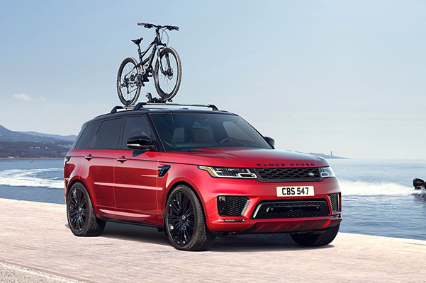 Rear view of a 2021 Range Rover Sport driving down a scenic road