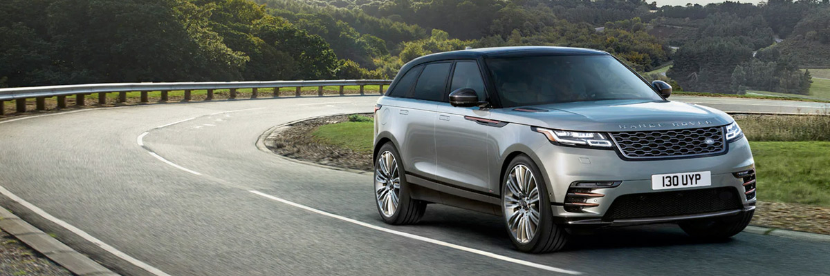 Range Rover Velar driving along a country road.