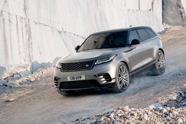 Range Rover Velar driving downhill on rocky terrain.