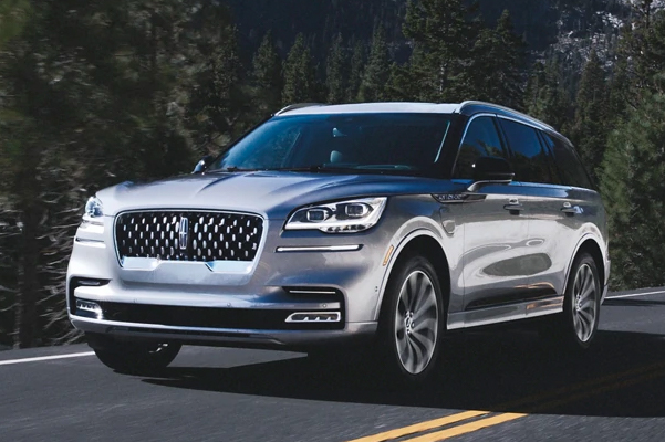 A 2021 Lincoln Aviator Grand Touring model is shown being driven on a tree lined road