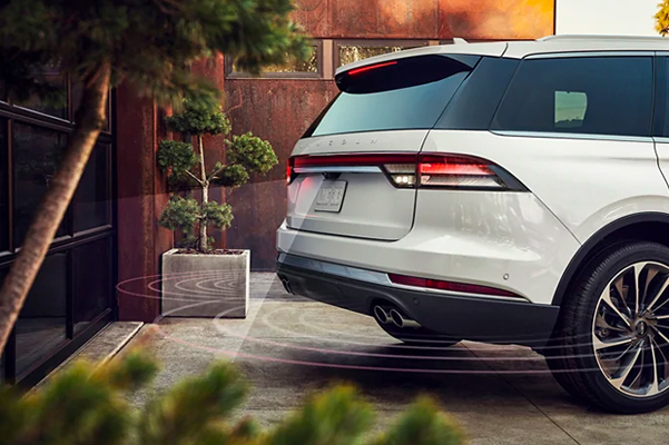A 2021 Lincoln Aviator is shown as it is backing up dangerously close to a garage door