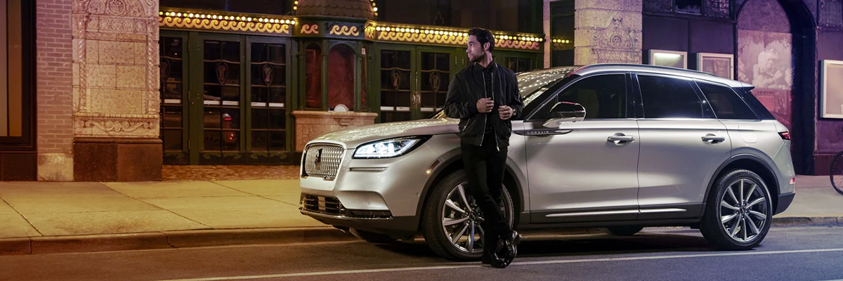 A 2021 Lincoln Corsair is parked outside a theatre as the driver relaxes against the frame and lights illuminate the floating roofline and body