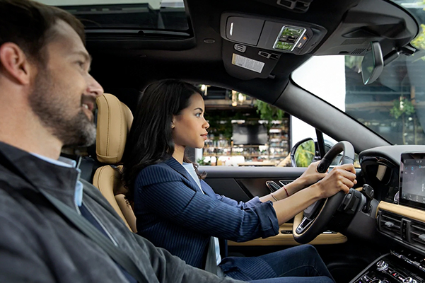 A woman in a blue pantsuit is driving a 2021 Lincoln Corsair through the city during the day as her male passenger speaks to Lincoln plus Alexa
