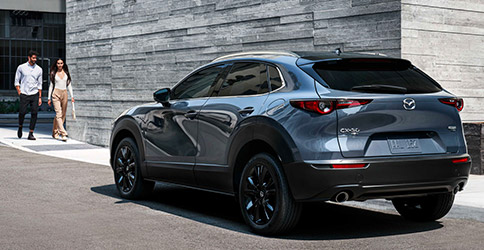 rear profile of Mazda CX-30 suv in blue color parked in front of commercial building