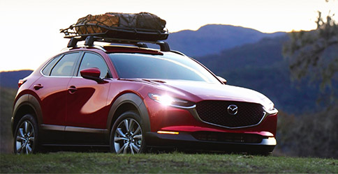 frontal profile of Mazda CX-30 suv in red color with headlights on, and luggage on top of the roof racks