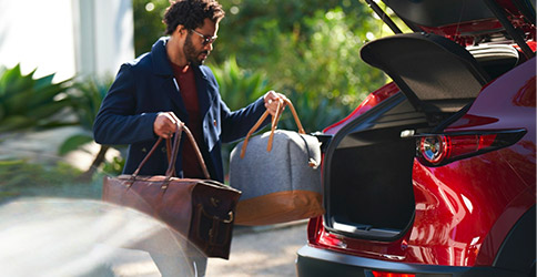 an african american man with two bags in his hands with the trunk open of the Mazda CX-30 suv
