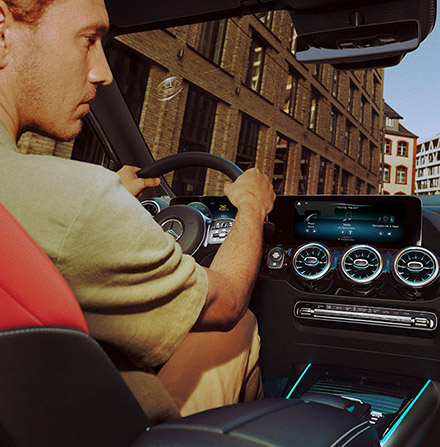 a man talking staring at a screen of the mercedes Benz gla featuring Mercedes-Benz User Experience (MBUX)