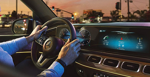 close up of hands on steering wheel inside the mercedes benz G L E showcasing digital screen with m b u x