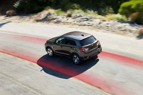 A 2021 Mitsubishi Outlander Sport on a highway with red stylized lines to either side of it to represent the vehicle's safety rating and features.