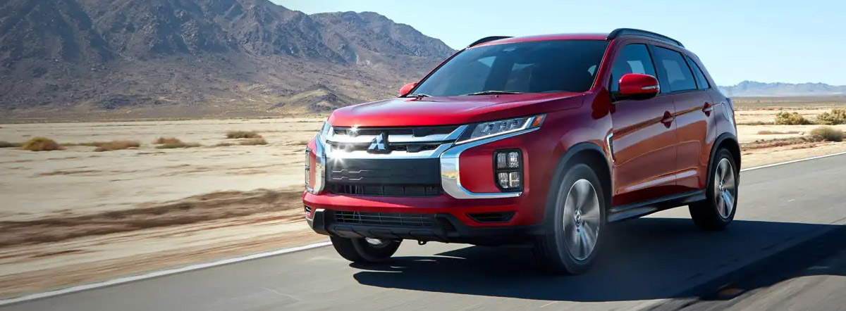 A red 2021 Mitsubishi Outlander Sport driving down a desert road on a beautiful sunny day.