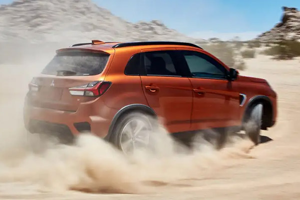 An orange 2021 Mitsubishi Outlander Sport spraying dust as it races through an open desert.