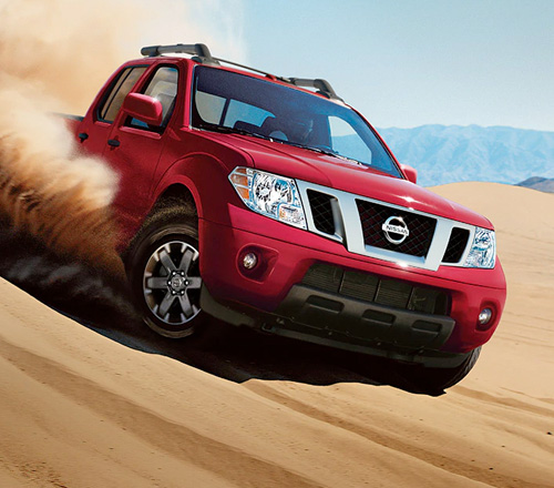 2021 Nissan Frontier in Red Metallic driving down a dune face