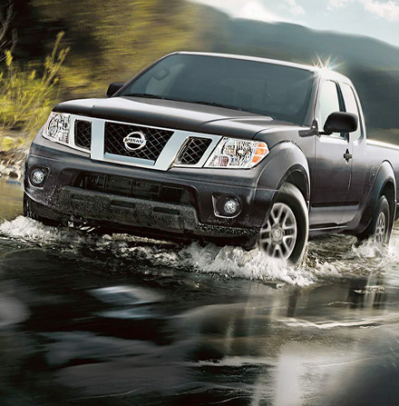 2021 Nissan Frontier in Magnetic Black Metallic driving in river bed