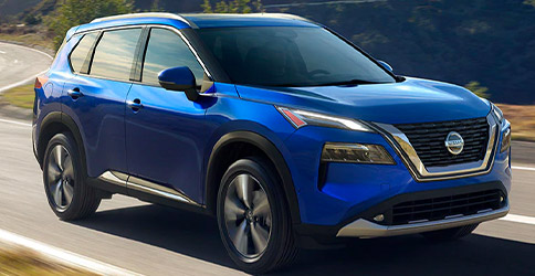 Blue Nissan Rogue driving in the mountains